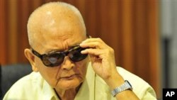 Noun Chea, former deputy secretary of the Communist Party of Kampuchea, adjusts his sunglasses during a joint hearing with other top Khmer Rouge leaders, Khieu Samphan, its head of state, and Ieng Thirith, former social affairs minister, at the outside th