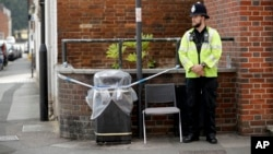 A British police officer guards a cordon around a plastic covered trash bin near John Baker House for homeless people in Salisbury, England, July 5, 2018.