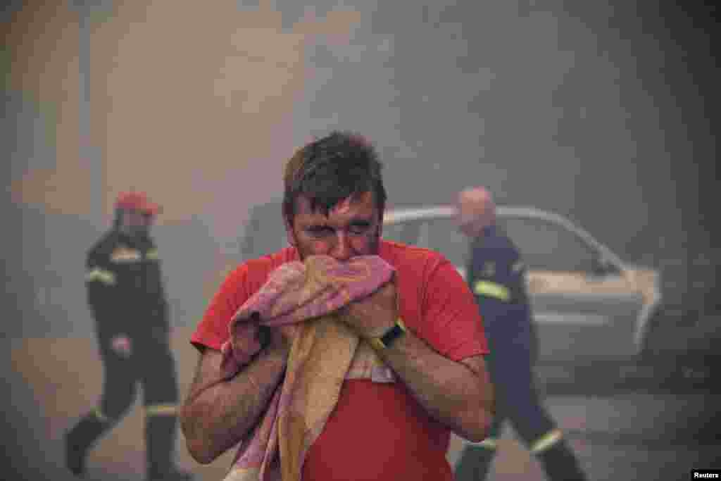 A man reacts to smoke as a wildfire burns at the village of Kontodespoti, on the island of Evia, Greece.