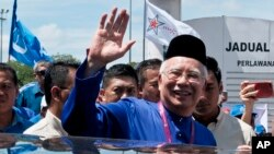 FILE - Malaysian Prime Minister Najib Razak waves to his supporters after his election nomination in Pekan, Pahang state, Malaysia, April 28, 2018.