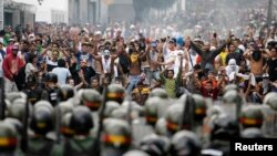 FILE - Supporters of opposition leader Henrique Capriles face off against riot police as they demonstrated for a recount of the votes in Sunday's election, in Caracas, April 15, 2013.