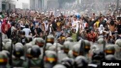 Para pendukung tokoh oposisi Henrique Capriles berhadap-hadapan dengan polisi anti huru-hara di Caracas (15/4). Ratusan pendukung oposisi bentrok dengan petugas keamanan Senin 16/4.