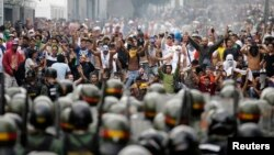 Supporters of opposition leader Henrique Capriles face off against riot police as they demonstrated for a recount of the votes in Sunday's election, in Caracas, April 15, 2013. Hundreds of protesters clashed with police in the Venezuelan capital on Monday