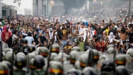 Supporters of opposition leader Henrique Capriles face off against riot police as they demonstrated for a recount of the votes in Sunday's election, in Caracas, Apr. 15, 2013.