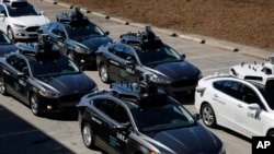 FILE - A group of self-driving Uber vehicles position themselves to take journalists on rides during a media preview at Uber's Advanced Technologies Center in Pittsburgh, Pennsylvania, Sept. 12, 2016.