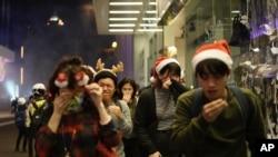 Warga mengenakan asesori untuk perayaan Natal menutup hidung dan matanya saat polisi menembakkan gas air mata untuk membubarkan para pengunjuk rasa di malam Natal di Hong Kong, 24 Desember 2019.