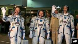 Astronot AS Karen Nyberg (kiri), Kosmonot Rusia Fyodor Yurchikhin (tengah) dan Astronot Italia Luca Parmitano berpose sebelum peluncuran roket Soyuz di Baikonur, Kazakhstan (28/5).