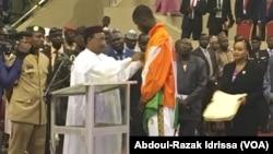 Abdoul-Razak Issoufou Alfaga, le champion du monde de taekwondo, reçoit une médaille du président Issoufou Mahamadou, 25 août 2016. (VOA/Abdoul-Razak Idrissa)