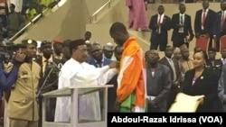 Le président Issoufou Mahamadou décorant le taekwondoïste de l'Ordre national du Niger, le 25 août 2016. (VOA/Abdoul-Razak Idrissa)