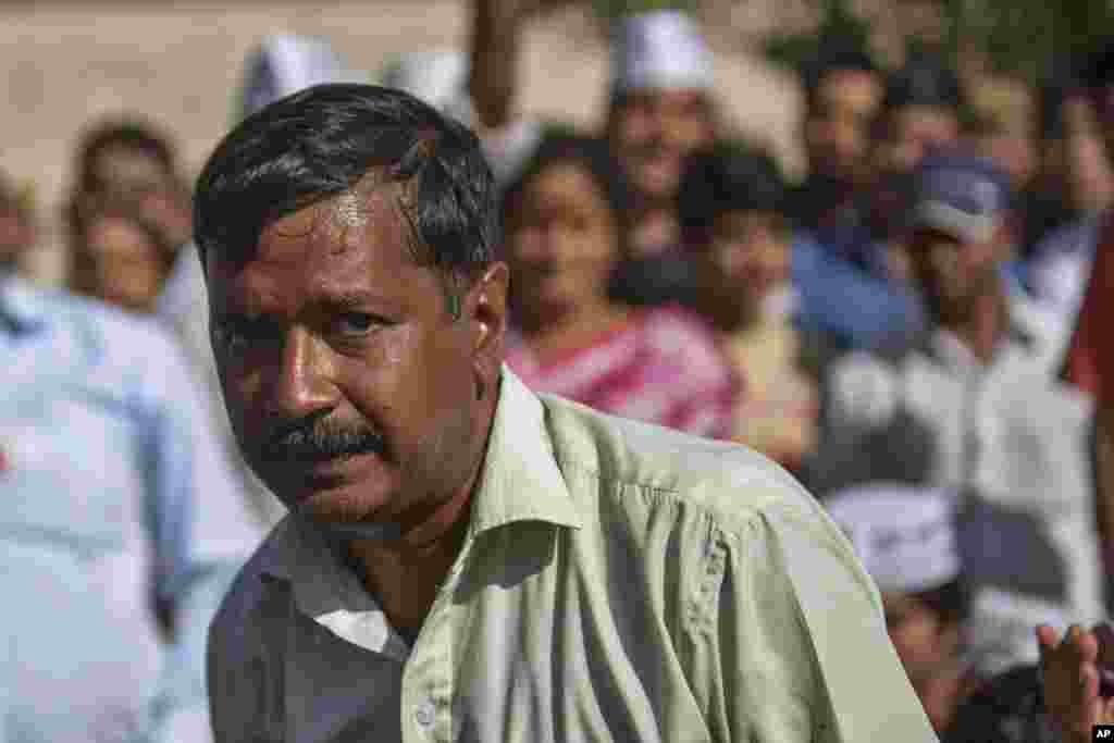 Aam Aadmi Party (AAP), or common man party, chief Arvind Kejriwal sits with supporters at Rajghat, the memorial of Mahatma Gandhi after he was slapped by an attacker during his election campaign in New Delhi, India, Tuesday, April, 8, 2014. The AAP party