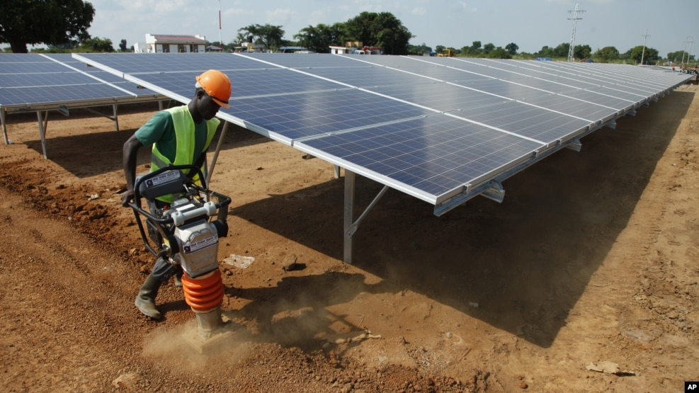 In this photo taken June 30, 2016, a Ugandan worker levels the ground at a solar plant in Soroti about 300 kilometers east of Uganda capital Kampala.