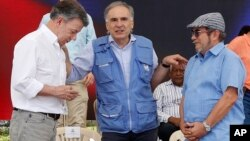 Jean Arnault, U.N. representative for the Colombian peace process, center, talks to Colombia's President Juan Manuel Santos, left, and Rodrigo Londono, the top commander of the Revolutionary Armed Forces of Colombia, FARC, during an act to commemorate the completion of the disarmament process of FARC rebels, in Buenavista, Colombia, Tuesday, June, 27, 2017.