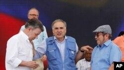 Jean Arnault, perwakilan PBB untuk proses perdamaian Kolombia (tengah), berbicara dengan Presiden Kolombia Juan Manuel Santos (kiri) dan Rodrigo Londono, yang juga dikenal sebagai Timoleon Jimenez (Timochenko), komandan tertinggi Angkatan Bersenjata Revolusioner Kolombia (FARC), dalam proses pelucutan senjata pemberontak FARC, di Buenavista, Kolumbia, Selasa, 27 Juni 2017. (Foto: dok).