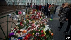 People look at flowers left for the plane crash victims at Dvortsovaya (Palace) Square in St. Petersburg, Russia, Nov. 2, 2015.