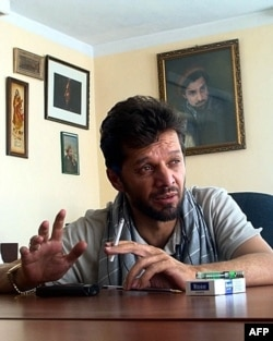 FILE - Afghan journalist Fahim Dashty speaks at his office in Kabul in this undated photograph. (Photo by STR/AFP)