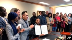 Shelby County, Tenn., Mayor Lee Harris, seated at desk, holds up a letter reaffirming Tennessee's largest county's commitment to keep resettling refugees, Jan. 3, 2020, in Memphis, Tennessee.