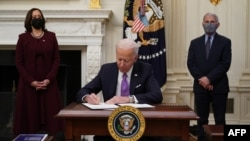 U.S. President Joe Biden signs executive orders as part of the COVID-19 response as U.S. Vice President Kamala Harris, left, and Director of NIAID Anthony Fauci look on in the State Dining Room of the White House in Washington, Jan. 21, 2021.