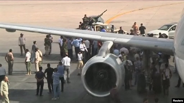 Airport officials negotiate with members of al-Awfea militia on the tarmac of Tripoli international airport in this still image taken from video June 4, 2012.