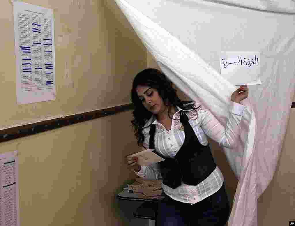 A woman comes out from behind a curtain after voting in parliamentary elections. (Reuters)