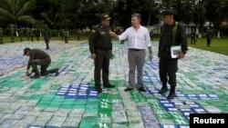 El presidente de Colombia, Juan Manuel Santos observa la 12 toneladas de cocaína incautada en Apartado, Colombia, el miércoles, 8 de noviembre de 2017.