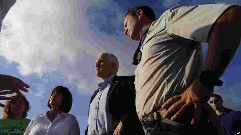 Le gouverneur de l'Indiana Mike Pence, et sa femme Karen, parlent avec des fonctionnaires de la Louisiane, le 19 août 2016.
