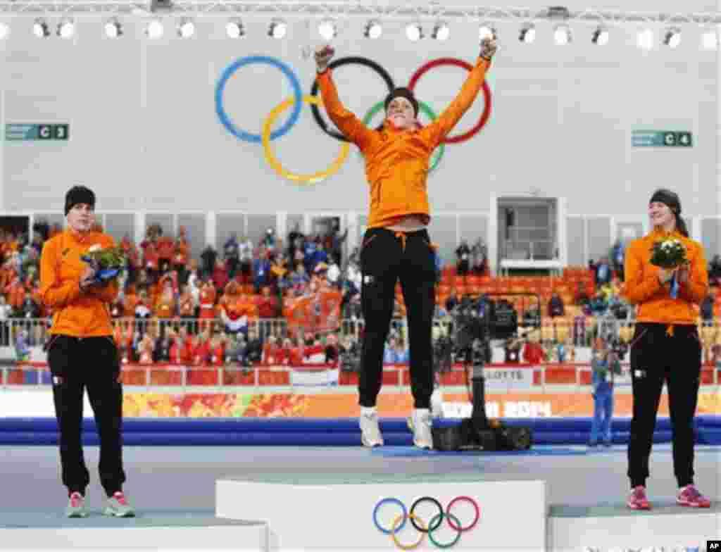 Gold medallist Jorien ter Mors of the Netherlands, center, jumps in celebration, applauded by country athletes, silver medallist Ireen Wust, left, and bronze medallist Lotte van Beek during the flower ceremony for the women's 1,500-meter speedskating race