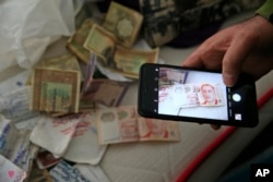 A member of the media uses his mobile phone to take pictures of belongings including banknotes of different currencies on a bed inside the flat where a suspect of New Year's Day nightclub attack was arrested during an overnight police raid, in Istanbul.