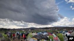 Des migrants s'apprêtent à se protéger dans leurs tentes à l'arrivée de la pluie près du poste-frontière grec d'Idomeni, le vendredi 4 mars 2016.