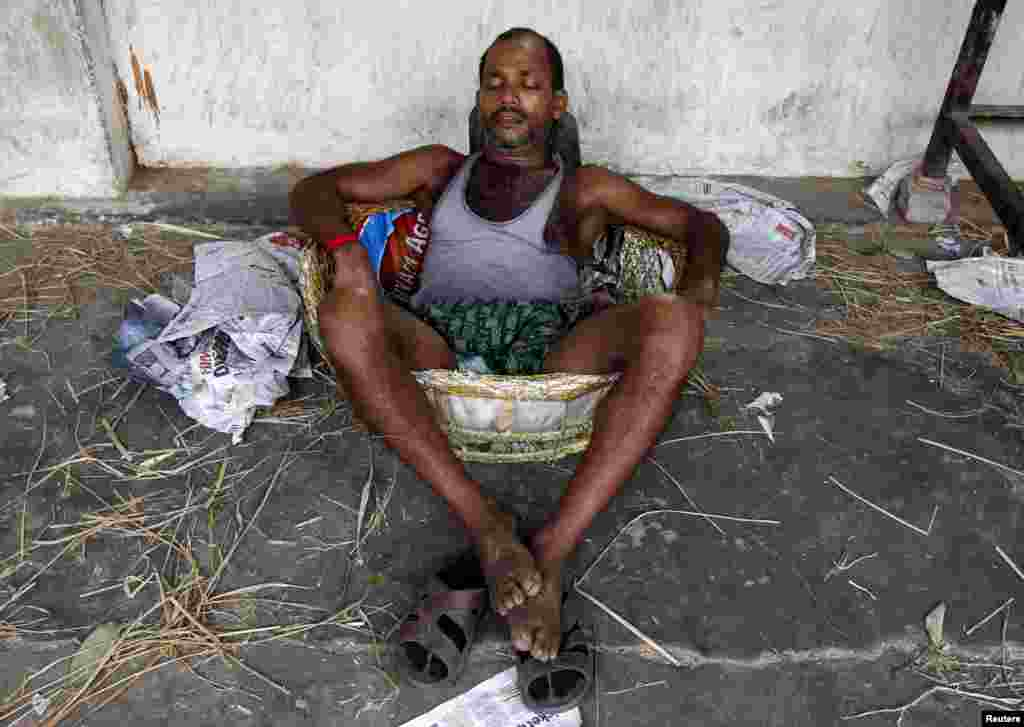 A laborer takes a nap in a basket at a wholesale vegetable market during a heat wave in Kolkata, May 25, 2015.