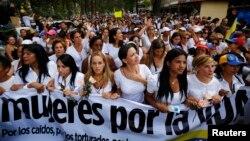 Maria Corina Machado (mano sobre el pecho) y Lilian Tintori (centro), esposa del encarcelado líder Leopoldo López, participan en una manifestación de mujeres en Caracas.