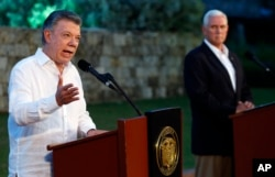 FILE - Colombia's President Juan Manuel Santos, left, talks to the media as U.S. Vice President Mike Pence listens during a joint press conference at the presidential guesthouse in Cartagena, Colombia, Aug. 13, 2017.