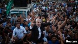 26일 이스라엘과 팔레스타인 하마스가 휴전에 합의한 후, 하마스 대변인 파우지 바르훔(가운데)이 가자지구에서 승리를 주장하며 축하하고 있다.
