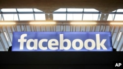 FILE - The Facebook logo is displayed at a gathering for startup companies at Paris' Station F., Jan. 17, 2017.