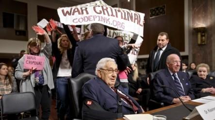 基辛格(左)和舒尔茨与奥尔布赖特三位前国务卿在参议院军事委员会作证时,抗议者干扰会场。(2015年1月29日)