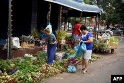 Women buy medicinal plants in Asuncion, Paraguay, on April 2, 2020.