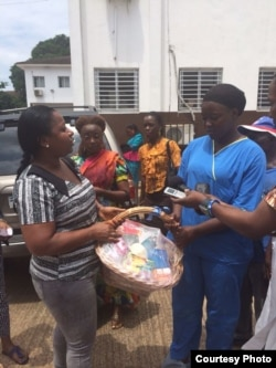 Power Women 232, a network of Sierra Leone professional women, distributes food baskets to show health care workers at Connaught Hospital in Freetown. At left is Asmaa James, the group's vice president and studio manager of Radio Democracy. (Photo courtes