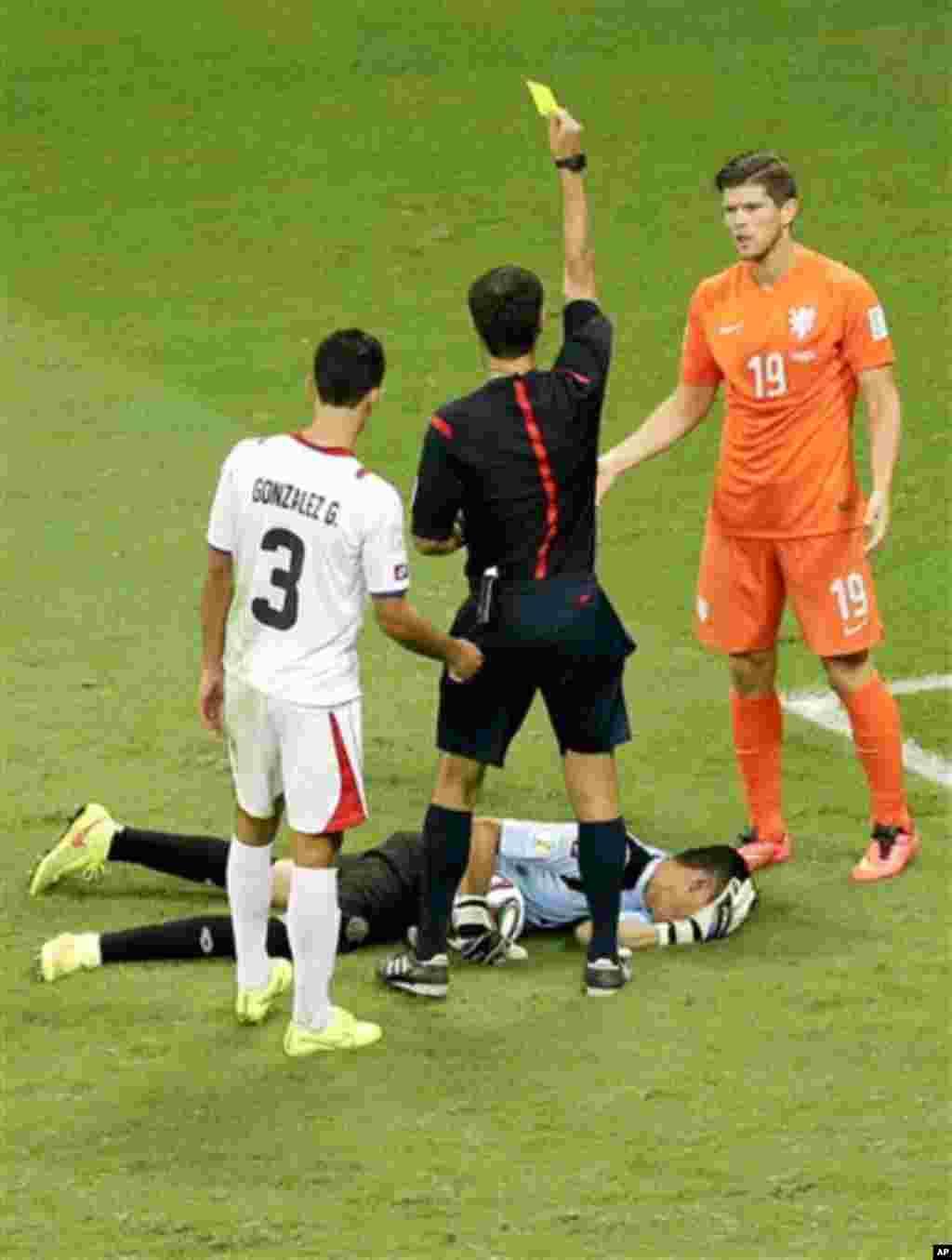 Netherlands' Klaas-Jan Huntelaar gets a yellow card for fouling Costa Rica's goalkeeper Keylor Navas during the World Cup quarterfinal soccer match between the Netherlands and Costa Rica at the Arena Fonte Nova in Salvador, Brazil, Saturday, July 5, 2014.
