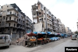 FILE - Stalls are seen on a street beside damaged buildings in the rebel held al-Shaar neighborhood of Aleppo, Syria, Feb. 10, 2016.