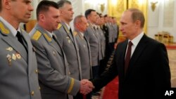 Russian President Vladimir Putin, right, shakes hands at the presentation ceremony of the top military brass in the Kremlin in Moscow, Russia, March 28, 2014