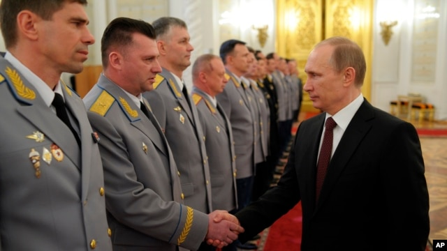 "Russian President Vladimir Putin, right, shakes hands with his generals in Moscow, Russia, Friday, March 28, 2014. The generals are the ""top brasses"" but Putin is the ""big cheese"" in Russia."