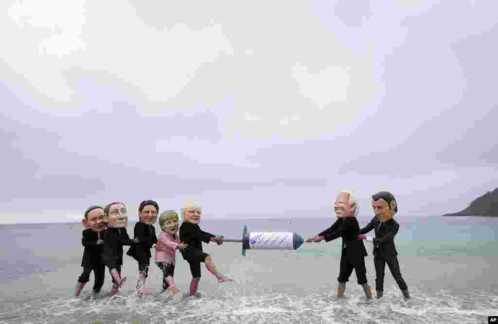 Activists wearing giant heads of the G7 leaders tussle over a giant COVID-19 vaccine syringe during an action of NGO's on Swanpool Beach in Falmouth, Cornwall, England.