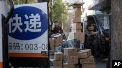 """中國""""光棍節""""當天,北京街頭快遞小哥在分發運送包裹(2019年11月11日)"""