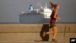 FILE - A woman is seen jogging on the Malecon as a cruise ship arrives in Havana bay, Cuba, March 19, 2015. Havana authorized, starting April 26, Cuban residents to enter and leave the island nation as passengers of cruise ships.