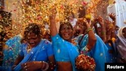 Các phụ nữ Ấn Ðộ ném hoa trong buổi lễ tại thị trấn hành hương Vrindavan, ngày 24/3/2013.