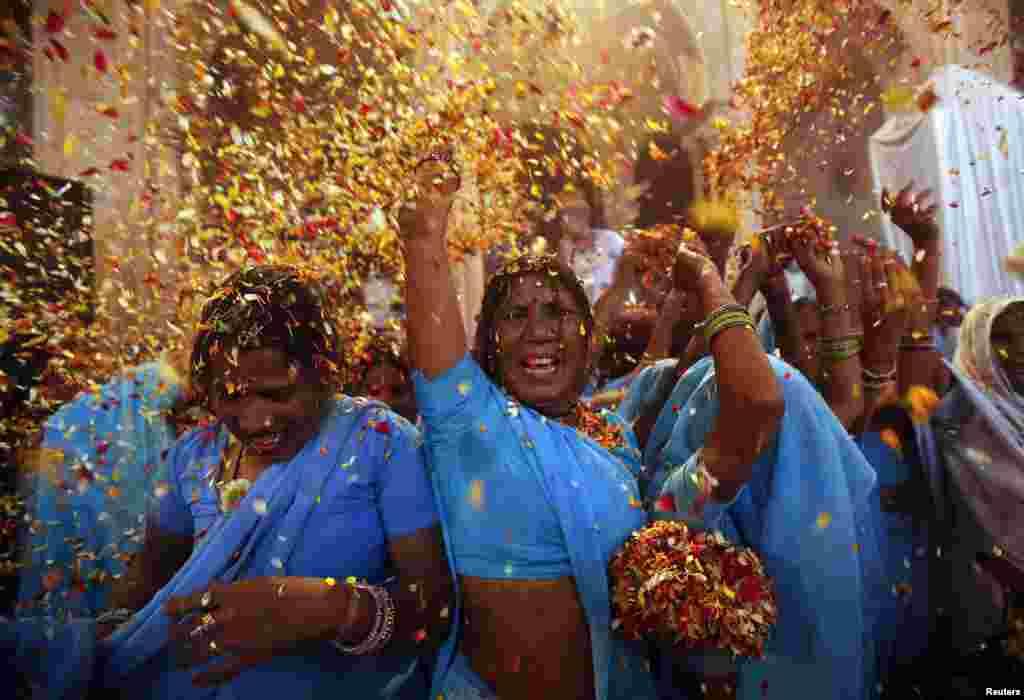 Các bà góa tung hoa và bột màu lên trời trong lễ hội Holi ngày 24/3/2013. Lễ hội Holi chào mừng mùa Xuân bắt đầu và được cử hành trên khắp Ấn Độ.