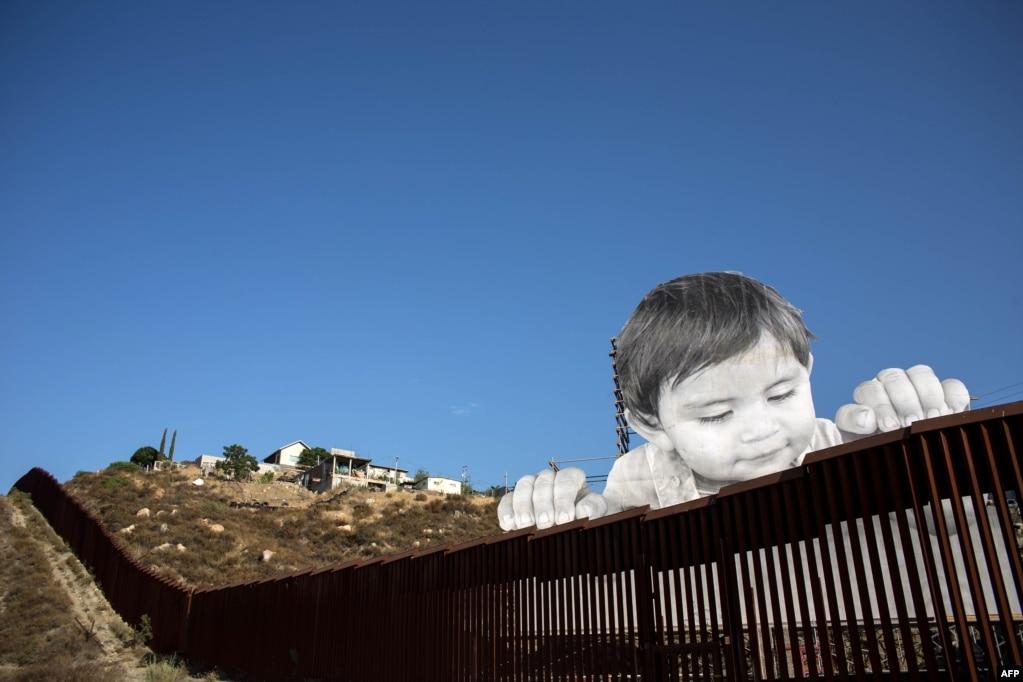 프랑스 예술가 JR이 미국 캘리포니아주 테카테 인근 멕시코 국경장벽에 설치한 조형물.