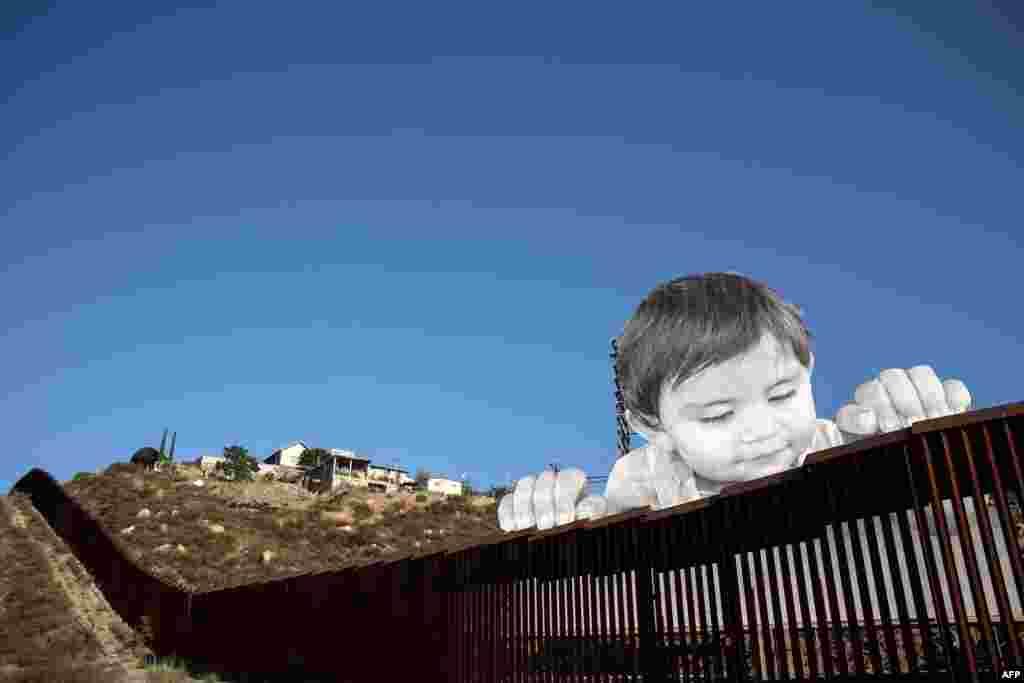 """Karya seniman Perancis """"JR"""" bergambar bayi memanjat pagar perbatasan AS-Meksiko di Tecate, California, AS."""