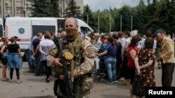 9일 우크나이나 슬로비얀스크 지역의 긴급의료시설 앞에 무장한 군인이 서 있다.