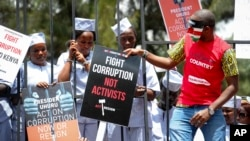 FILE - Demonstrators wear mock prison outfits to show that they want to imprison those engaged in corruption, in Nairobi, Kenya Thursday, Nov. 3, 2016.