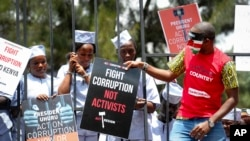 FILE - Demonstrators wear mock prison outfits to show that they want to imprison those engaged in corruption, in Nairobi, Kenya, Nov. 3, 2016. Kenya and Jersey signed a deal Thursday for the return of millions of dollars in graft money.